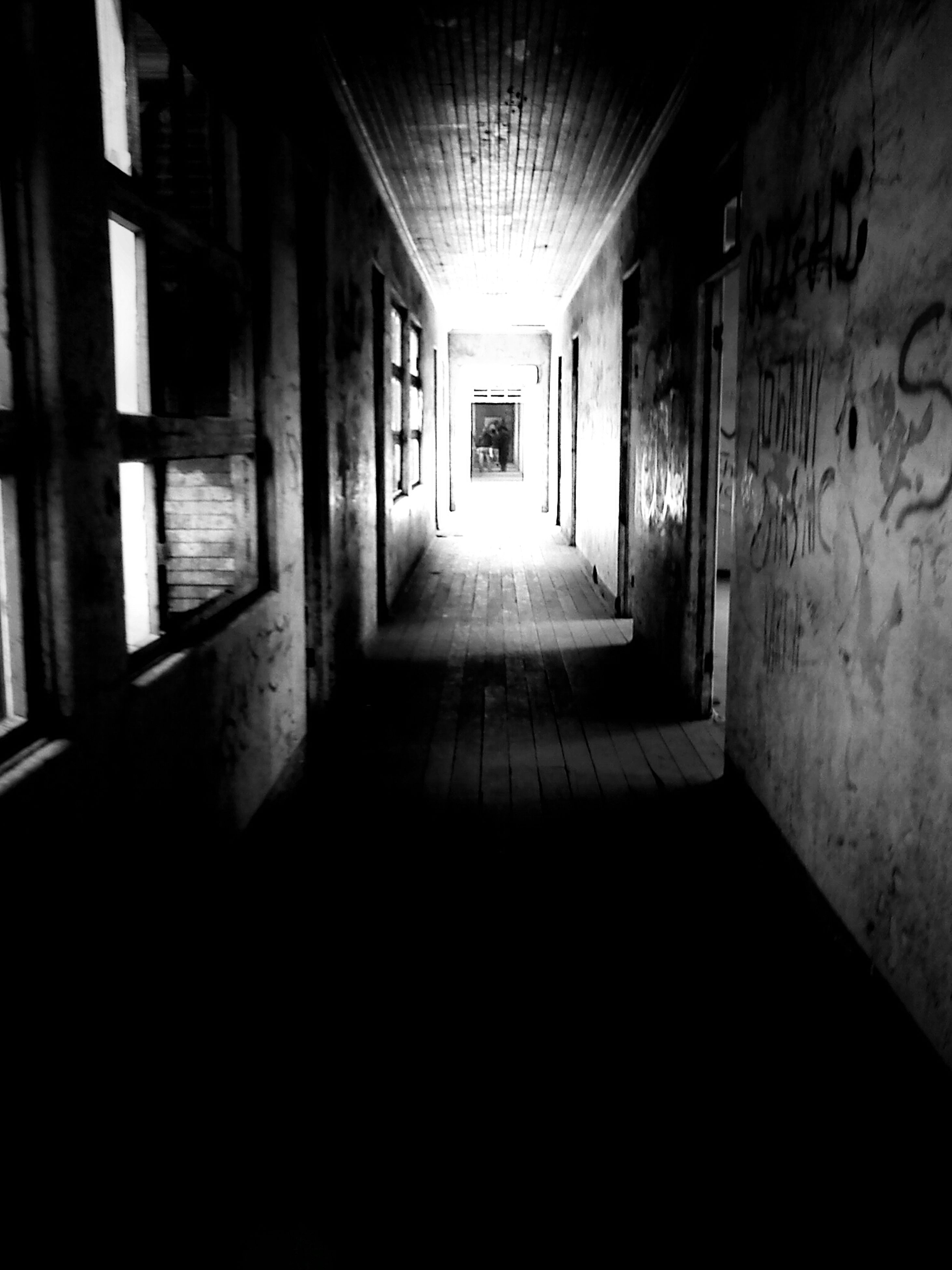 indoors, architecture, corridor, built structure, the way forward, illuminated, empty, wall - building feature, building, diminishing perspective, narrow, door, absence, flooring, wall, no people, interior, dark, ceiling, lighting equipment