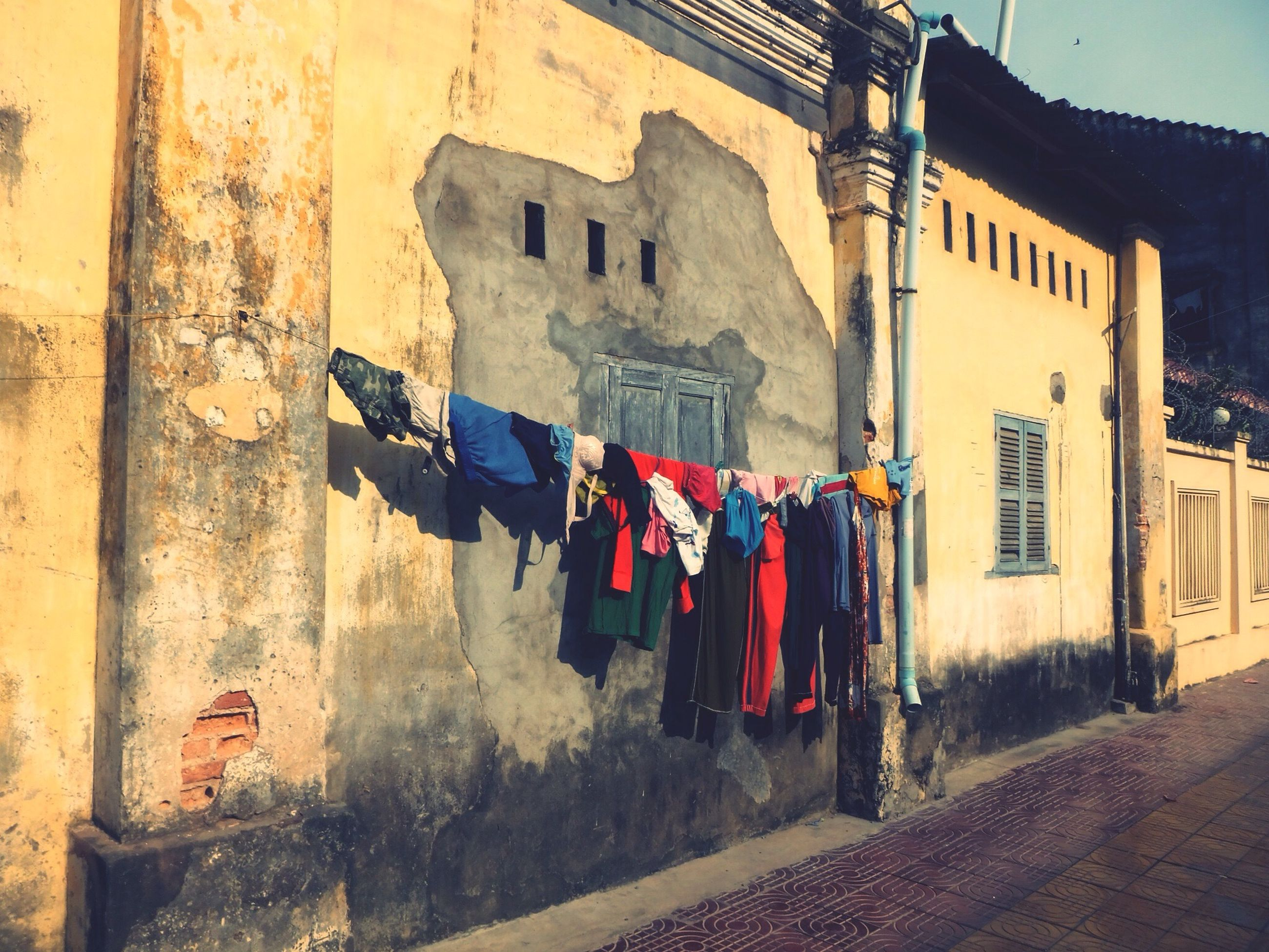 building exterior, architecture, built structure, multi colored, graffiti, residential building, wall - building feature, street, residential structure, house, day, building, outdoors, in a row, wall, no people, old, store, drying, variation