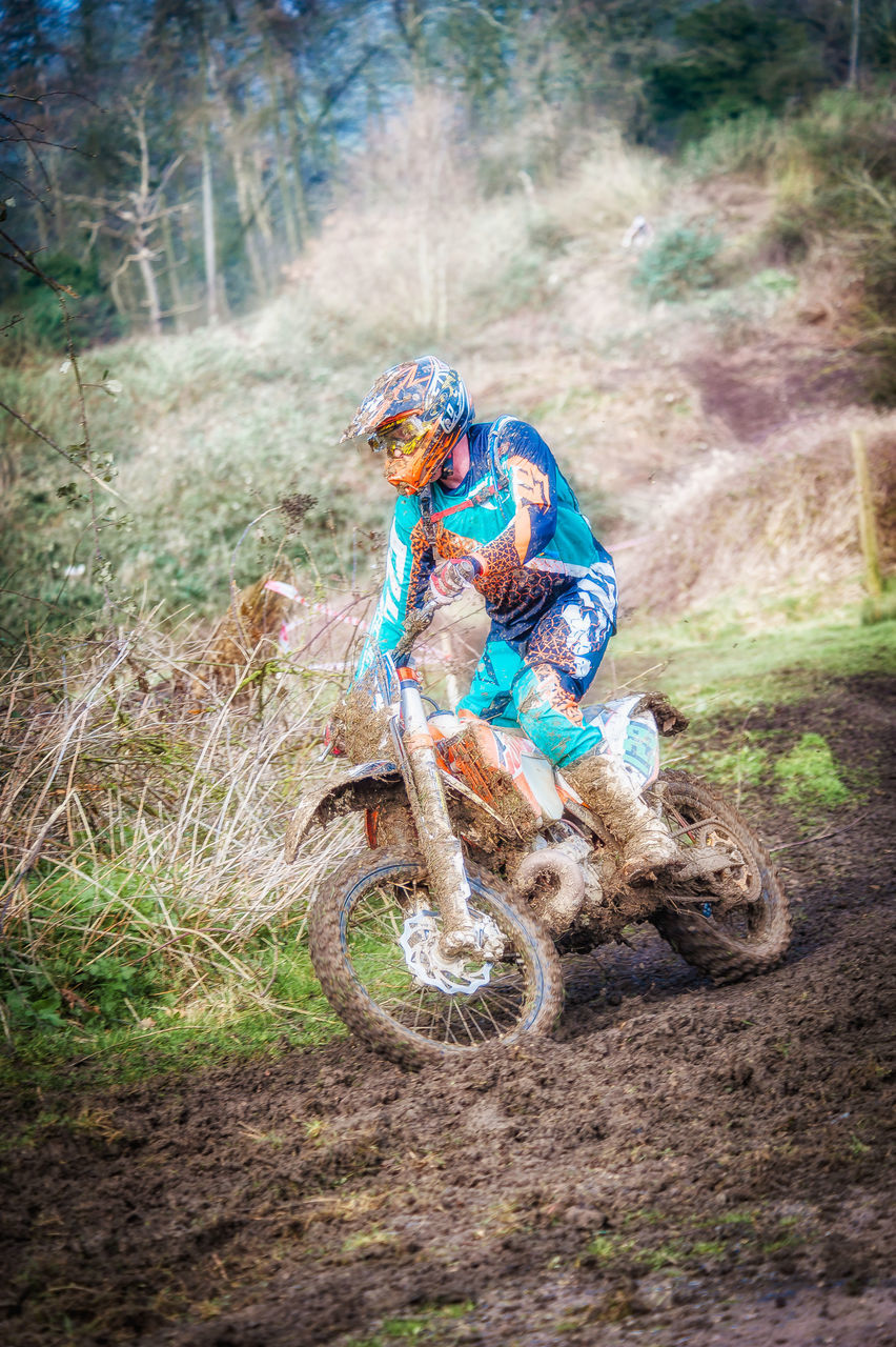 adventure, headwear, transportation, helmet, extreme sports, forest, day, speed, outdoors, field, nature, riding, motocross, sports helmet, one person, full length, sport, mountain bike, sports clothing, cycling helmet, motorcycle, men, sports track, grass, tree, one man only, people