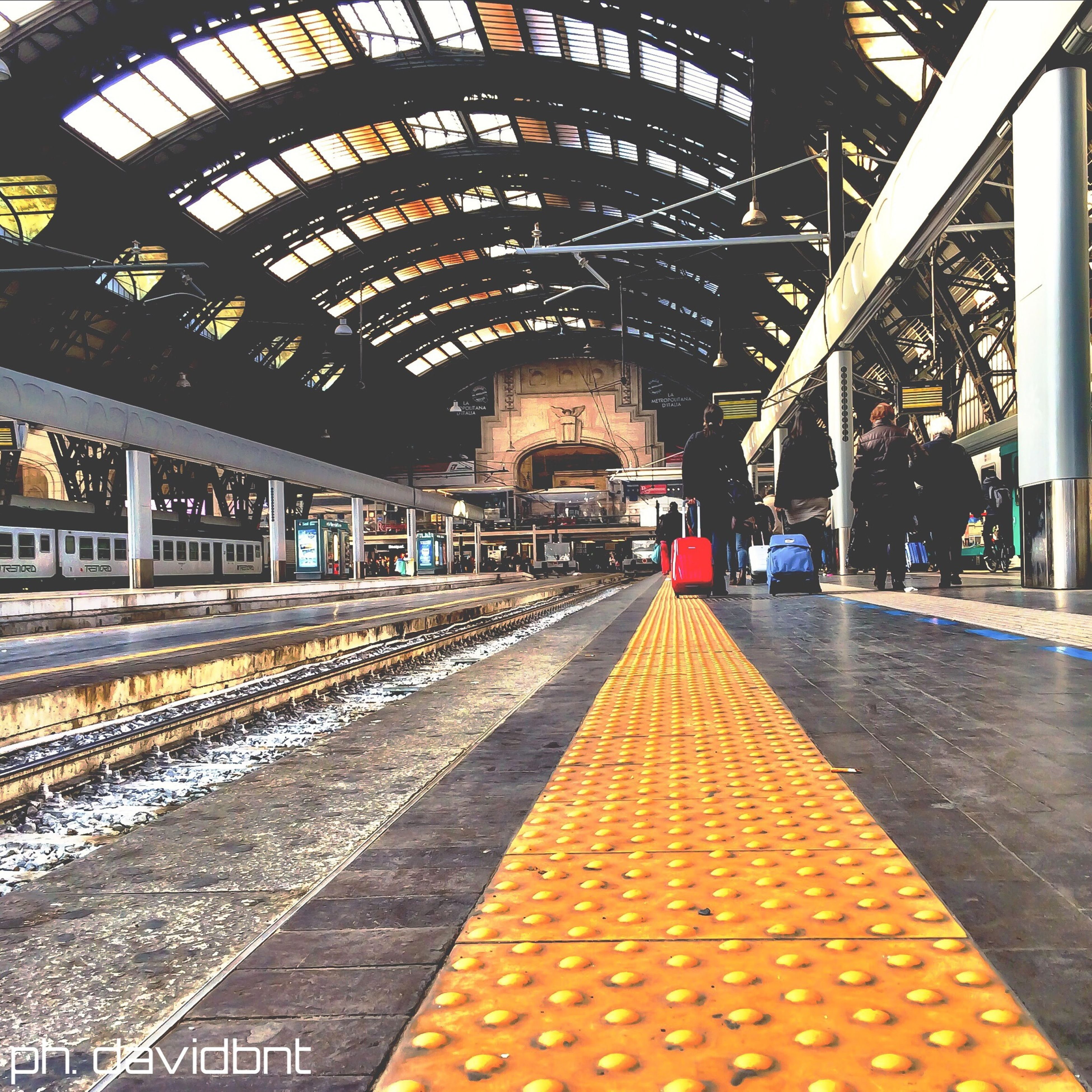 indoors, railroad track, rail transportation, ceiling, railroad station, public transportation, railroad station platform, diminishing perspective, the way forward, architecture, transportation, built structure, incidental people, illuminated, vanishing point, travel, subway station, subway, men
