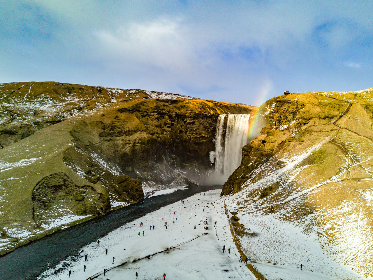 The famous Skógafoss falls, seen from high in the sky, with the last sun rays of the day illuminating the water splash to a small rainbow. Cold Temperature Dronephotography Falls Famous Place Flying High From Above  Iceland Landscape Mountain Nature Outdoors Rainbow Scandinavia Scenics Skogafoss Snow Tranquil Scene Tranquility Travel Destinations Waterfall Winding Road Winter