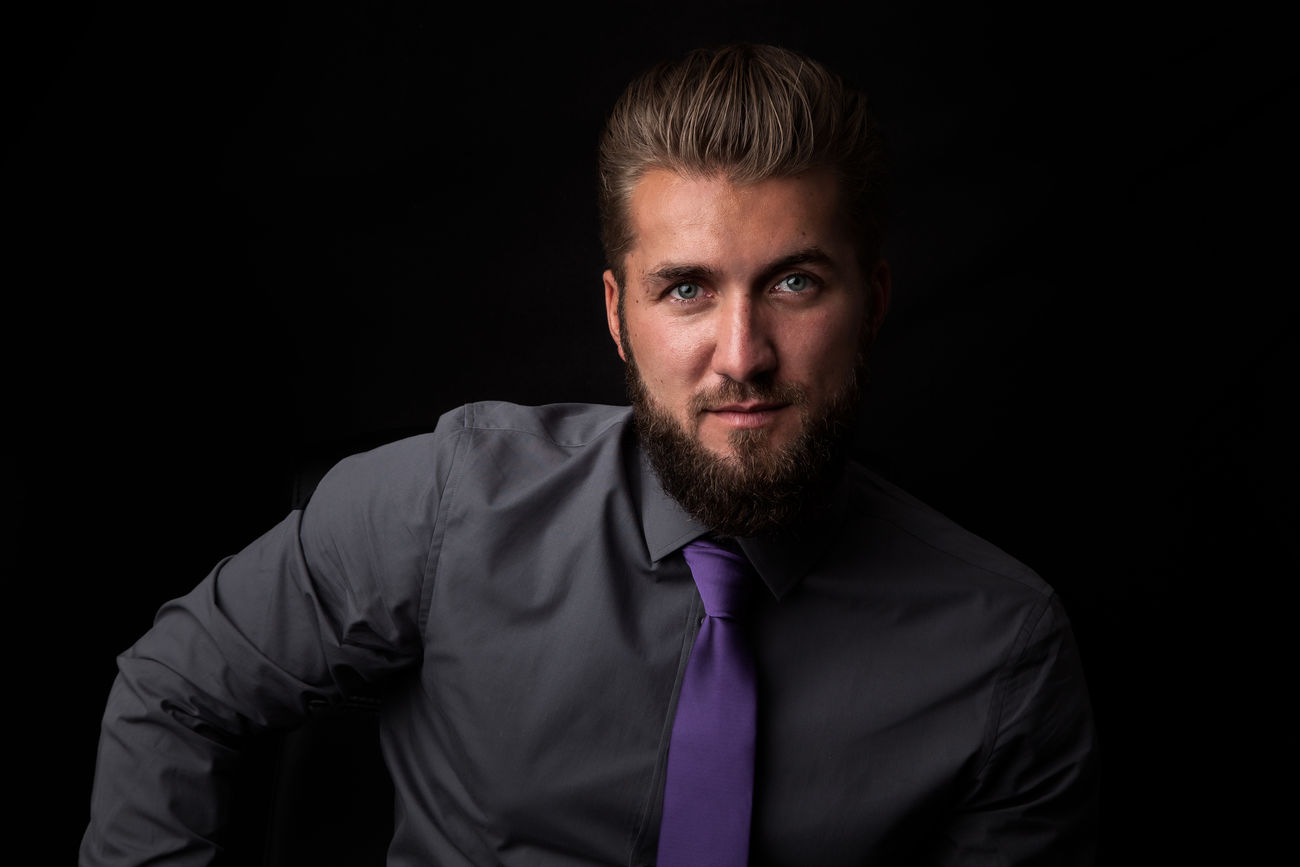 Attractive smiling businessman in front of a black background Adult Attractive Beard Bearded Black Background Botany Business Businessman Confidence  Elegant Lifestyle Lifestyles Looking At Camera Mafia  One Person People Portrait Proffessiona River Sitting Smiling Studio Shot Stylish Successful Young