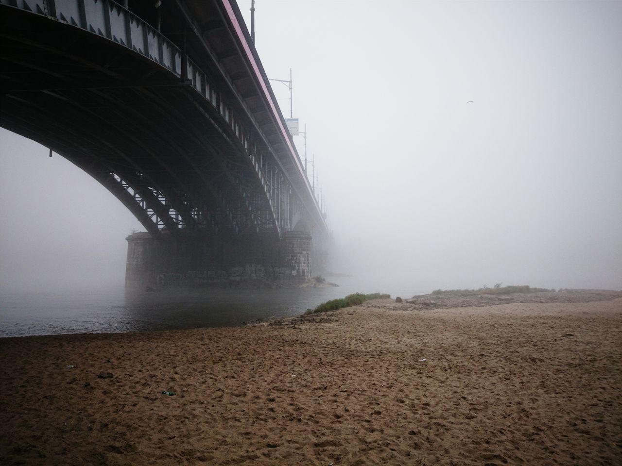 Low Angle View Of Bridge Through Fog