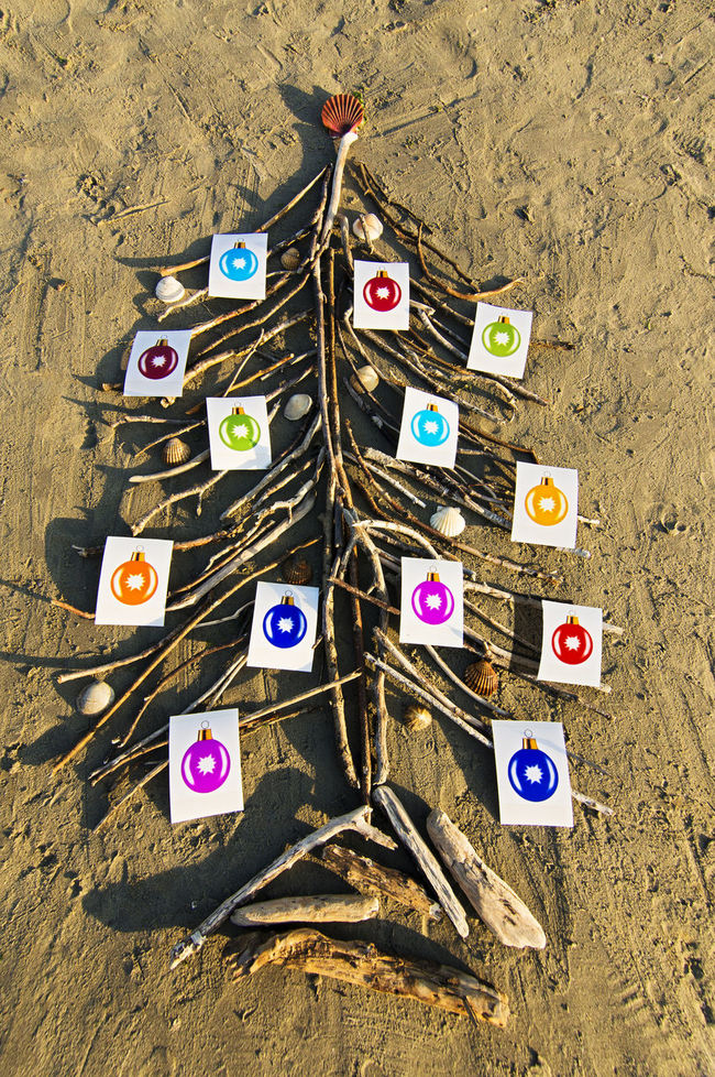 christmas balls photographs on tree made of branches on the beach at sunset Christmas Balls Christmas Decorations December Holiday Nativity Tradition Meets Modern Xmas Xmas Decorations Xmas Time Xmas Tree