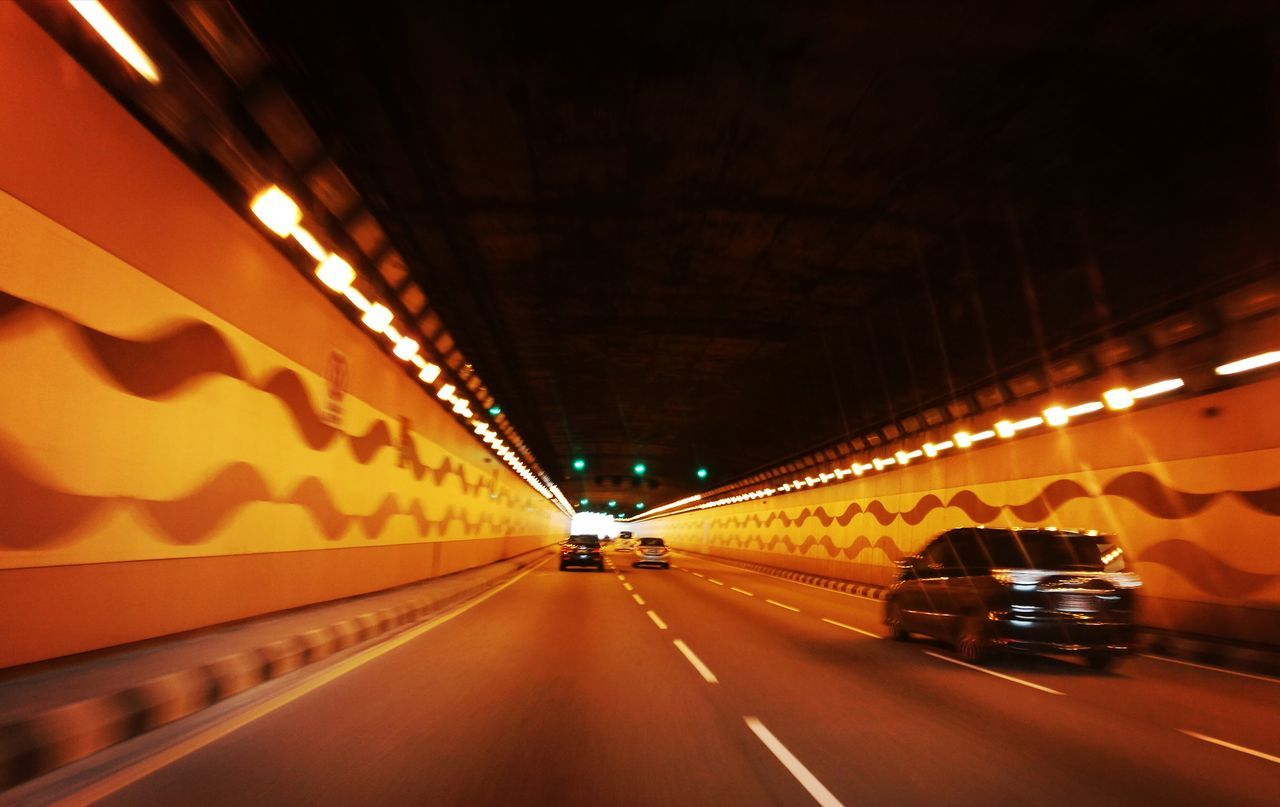 transportation, illuminated, the way forward, road, car, land vehicle, lighting equipment, diminishing perspective, speed, tunnel, mode of transport, dividing line, motion, night, bridge - man made structure, no people, yellow, outdoors, city