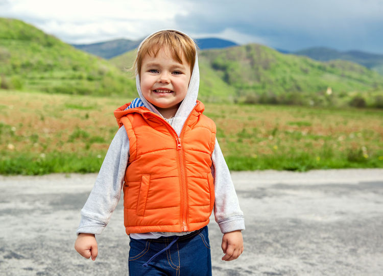 Adorable baby girl against green mountains Casual Clothing Caucasian Cheerful Child Childhood Cloud - Sky Day Green Hills Happiness Infant Kid Landscape Little Looking At Camera Mountain Mountain Range One Person Outdoors People Small Smiling Spring Springtime Standing