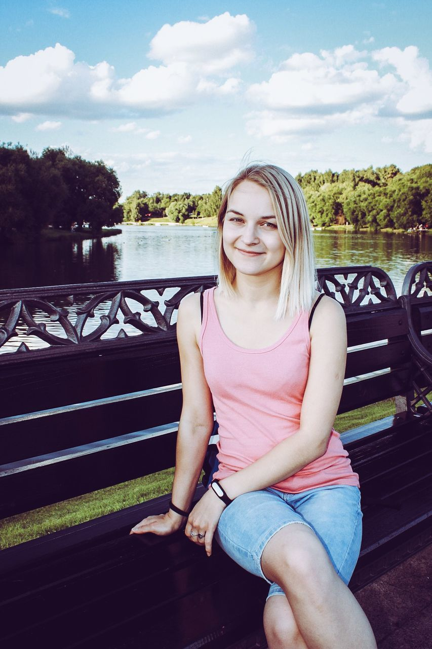 Portrait Of Smiling Young Woman Sitting On Bench By River Against Sky
