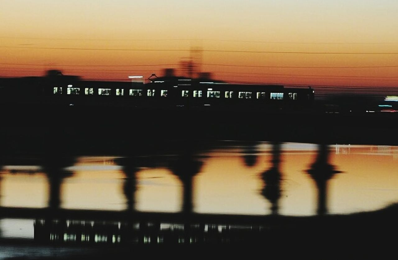 sunset, silhouette, blurred motion, transportation, river, outdoors, architecture, no people, built structure, illuminated, travel destinations, night, nature, city, sky