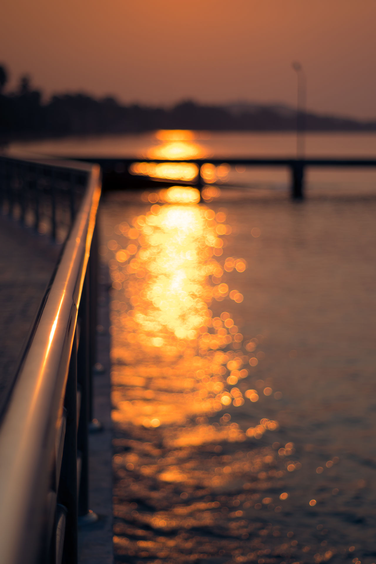 Soft glow of the sun reflecting on water with circular bokeh. Background Blur Bokeh Bridge Calm Circular Concept Glowing No People Orange Outdoors Railing Reflection Seascape Sky Summer Sun Sunrise Sunset Thailand Tranquil Scene Tranquility Travel Destinations Vacation Water
