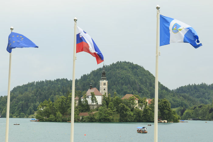 Bled, Slovenia - June 3, 2017: Close up of the church in the center of Bled Lake with several tourists on a boat Beauty In Nature Church Cottage Day Europe Flag Lake Lake Bled Lake Bohinj National Icon Nature No People Outdoors Patriotism Pride River Sky Slovenia Tourists Tree Velika Planina Water Waving Wind