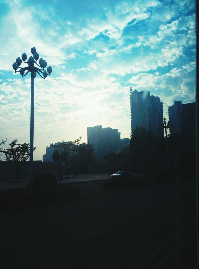 Building Exterior Built Structure City Street Car Street Light Architecture Sunset Road Sky Sun Tall Tall - High Lighting Equipment Lamp Post Cloud - Sky Skyscraper Cloud The Way Forward Outdoors PassingBy Sky And Trees Clouds And Sky Nature Makes Me Smile Taking Photos
