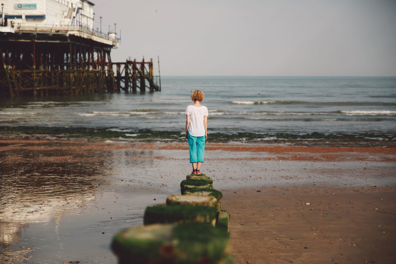 Rear View Of Woman Standing On Rock By Eastbourne Pier At Beach Against Sky