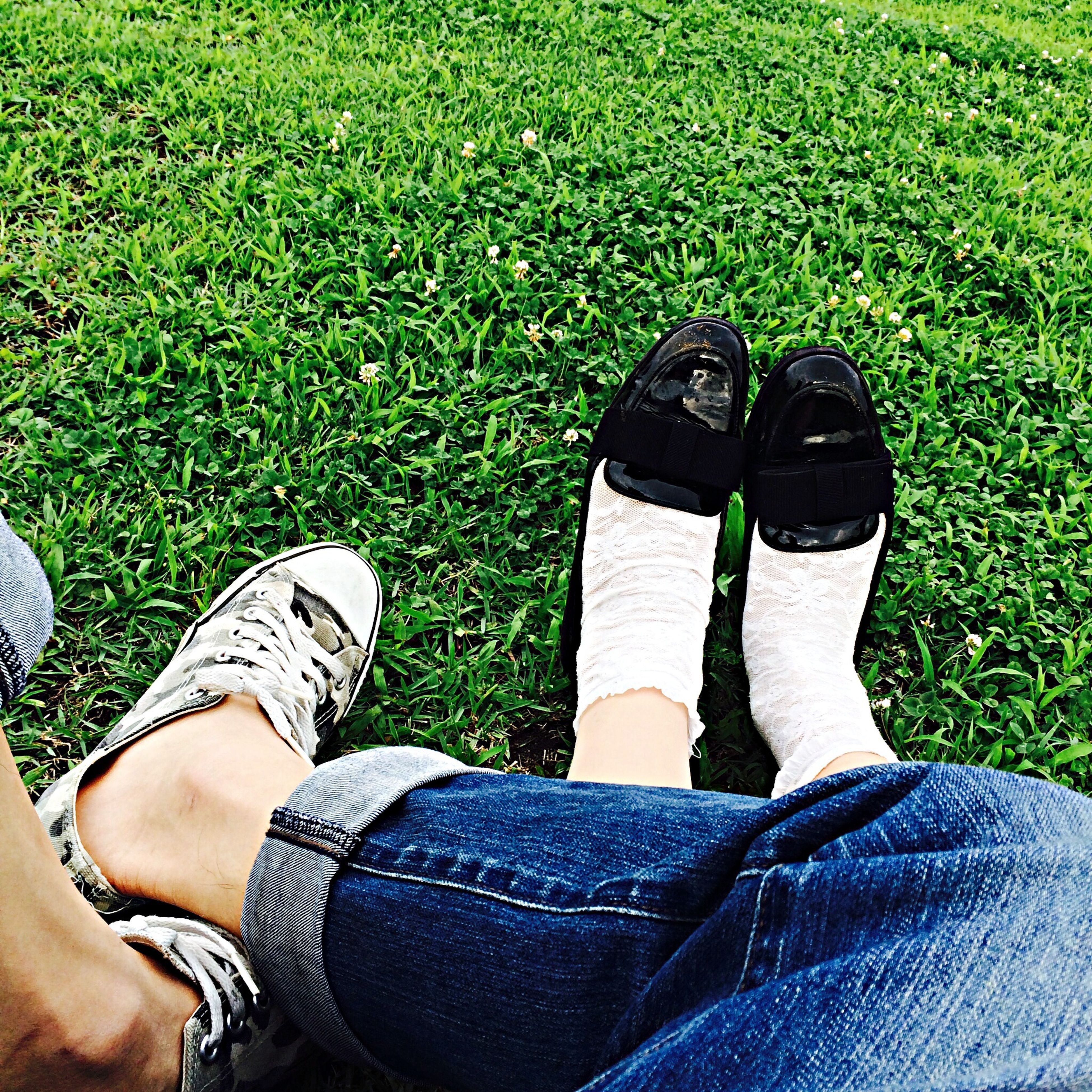 low section, person, shoe, personal perspective, footwear, grass, jeans, lifestyles, human foot, men, leisure activity, field, standing, grassy, high angle view, canvas shoe, sitting
