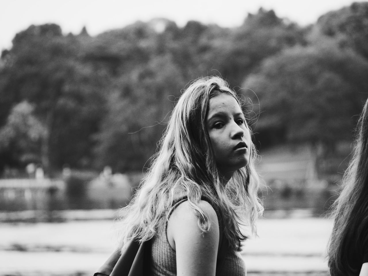 long hair, focus on foreground, blond hair, young adult, real people, young women, leisure activity, one person, lifestyles, beautiful woman, outdoors, day, portrait, looking at camera, close-up, nature, sky