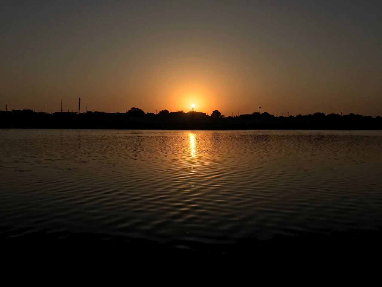 sunset, sun, silhouette, tranquility, reflection, water, nature, tranquil scene, beauty in nature, scenics, sky, orange color, no people, outdoors, idyllic, sunlight, waterfront, lake