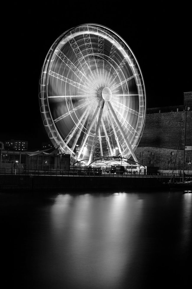 """Ferris wheel by night, a long exposure. [2/365] 2016.11.10 Together with my beloved one we decided to go on a little evening stroll down the streets of Gdańsk's old town. Being a wannabe photographer, by mere chance I happened to have with me my Fuji X-T1 together with the kit XF18-135mm f/3.5-5.6 LM OIS R WR lens and a couple of ND filters. Aaaand a tripod, obviously. Since not so long ago there's this """"observation wheel"""" so I thought maybe it'll look fun as a long exposure b&w photo. I've tried fiew different angles from different spots across the street by the Motława river. I used an 8 stop ND filter and estabilished that around 2 minutes of exposure give me the look I like. And this is the result. 365 365 Day Challenge 365project Architecture Big Wheel Built Structure Circle Ferris Wheel Illuminated Large Long Exposure Longexposure Night No People Reflection Water"""