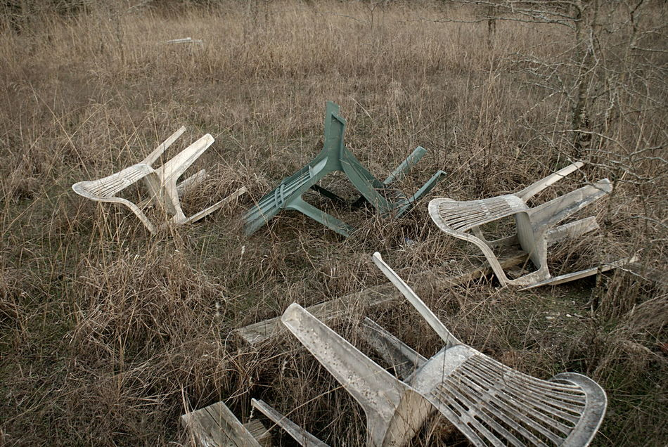 Plastic lawn chairs lie, blown over, in the tall winter grasses, at an abandoned camping spot in the countryside. Abandoned Chairs Countryside Field Grasses Mayhem  Nature Neutral Colors Plastic Rural Texas Texas Vintage Vintage Feel Wind Winter