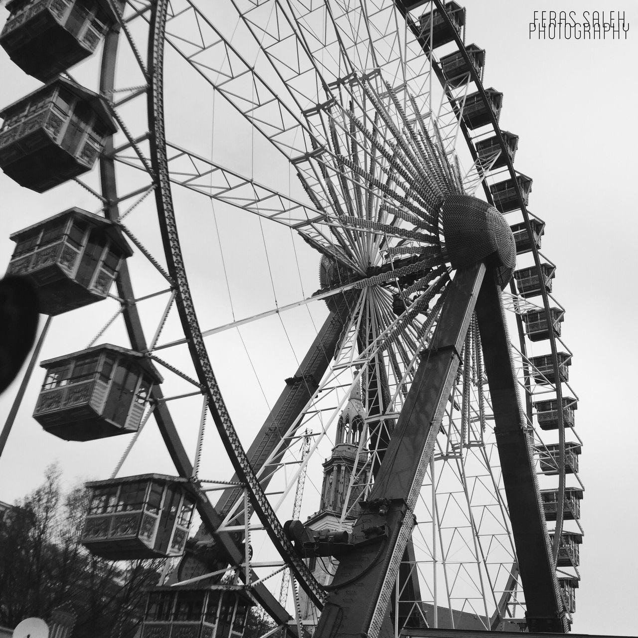 low angle view, built structure, architecture, amusement park, amusement park ride, arts culture and entertainment, ferris wheel, building exterior, sky, clear sky, travel destinations, leisure activity, day, outdoors, travel, tourism, tall - high, city, famous place