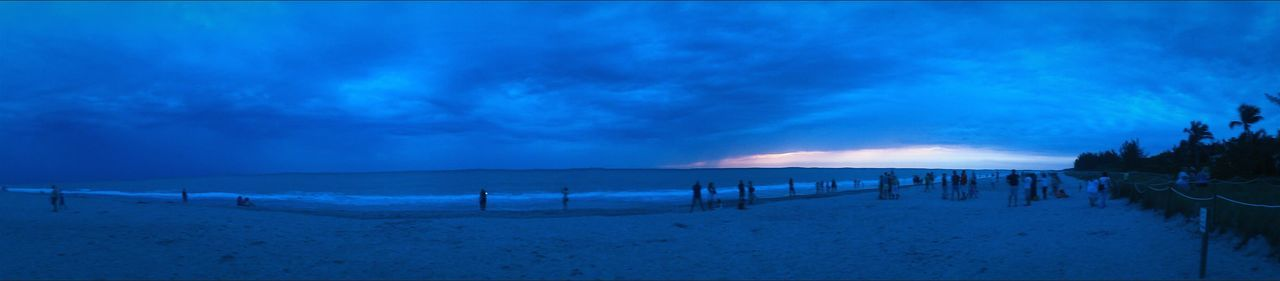 nature, cold temperature, scenics, sky, beauty in nature, beach, outdoors, sea, tranquility, tranquil scene, blue, cloud - sky, sand, winter, snow, panoramic, large group of people, water, sunset, day, people