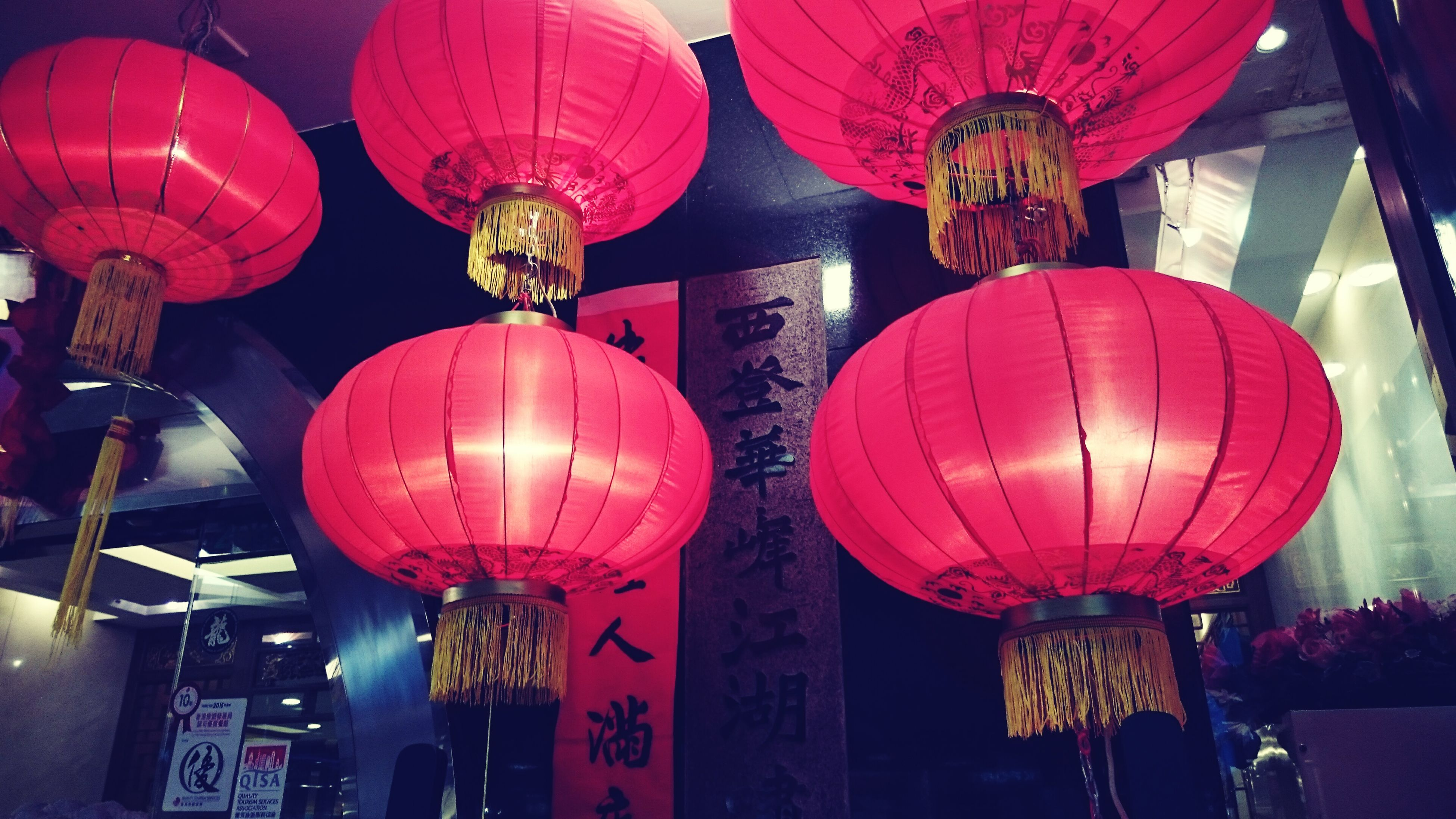 hanging, illuminated, lighting equipment, lantern, decoration, chinese lantern, low angle view, celebration, cultures, tradition, indoors, night, red, traditional festival, electric lamp, ceiling, electricity, electric light, culture, in a row