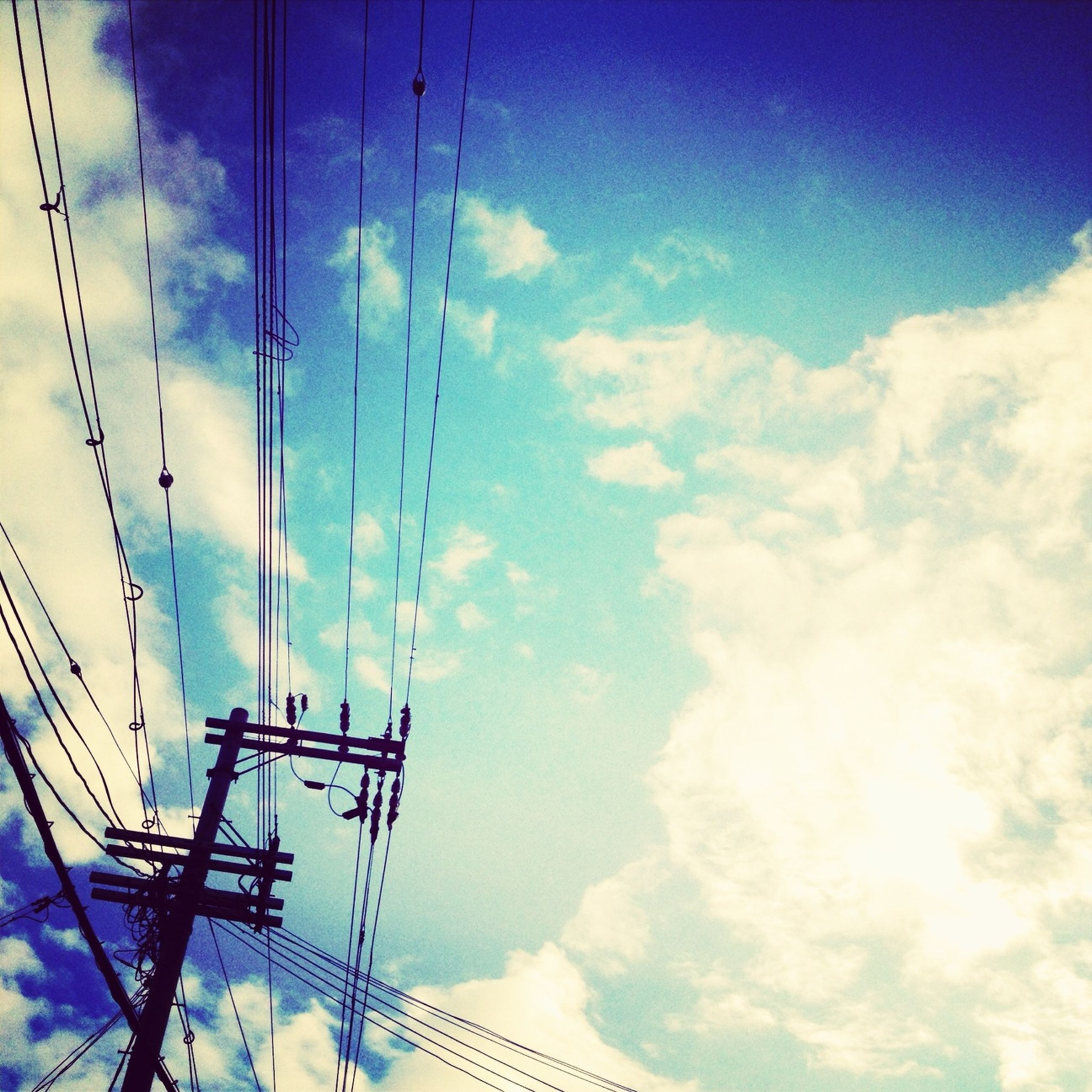 power line, low angle view, sky, electricity, electricity pylon, power supply, cable, connection, blue, cloud - sky, technology, fuel and power generation, cloud, cloudy, power cable, day, no people, outdoors, built structure, sunlight