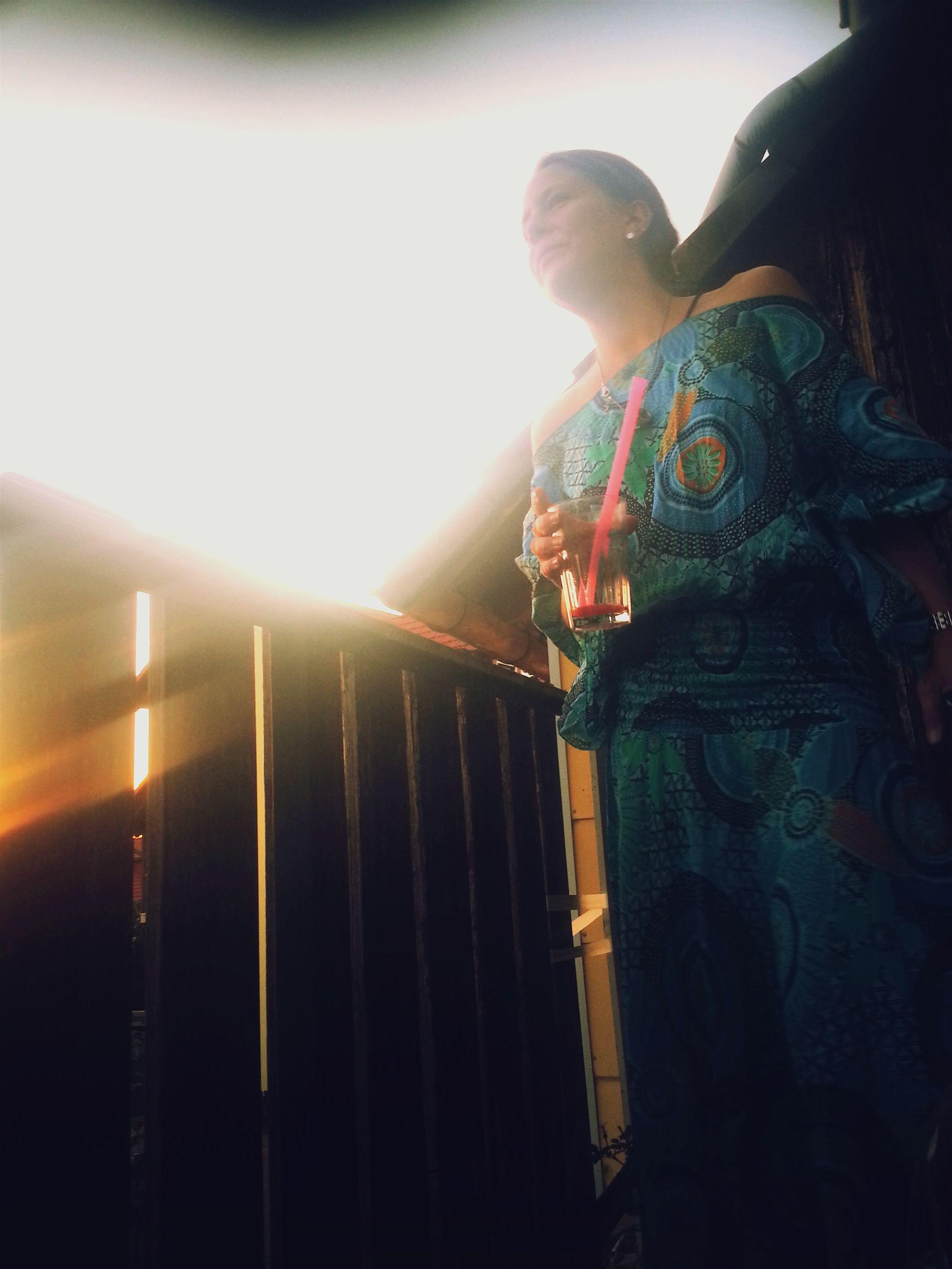 lifestyles, leisure activity, lens flare, rear view, illuminated, men, standing, casual clothing, sun, full length, sunbeam, sunlight, night, three quarter length, warm clothing, person, lighting equipment, indoors