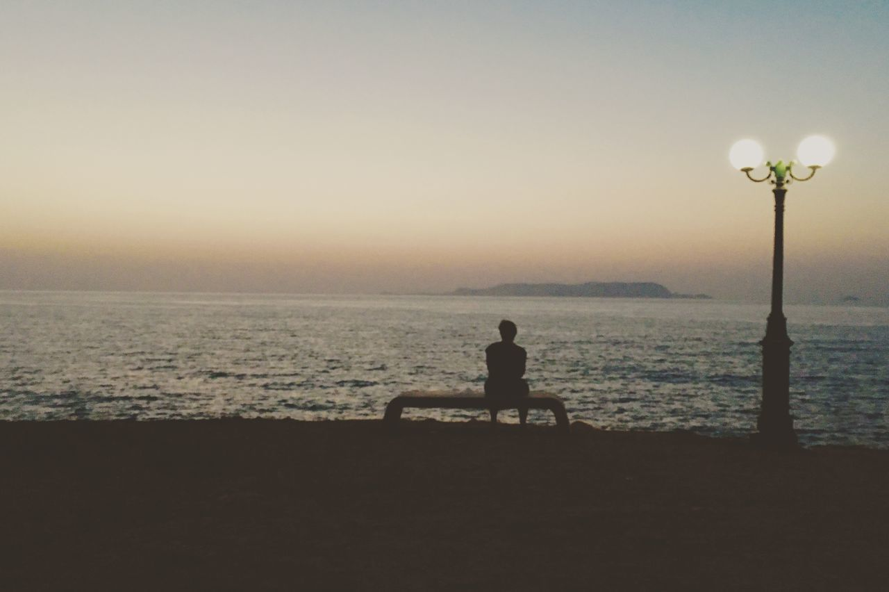 sea, nature, sitting, water, sunset, one person, silhouette, clear sky, real people, beach, outdoors, beauty in nature, scenics, sky, full length, lifestyles, horizon over water, day, people