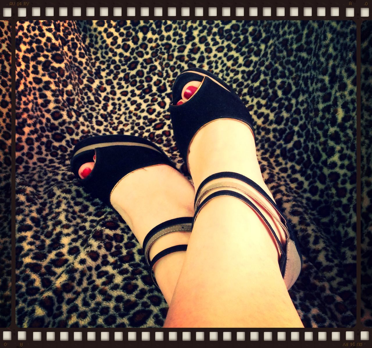 High angle view of woman wearing shoes on leopard print fabric