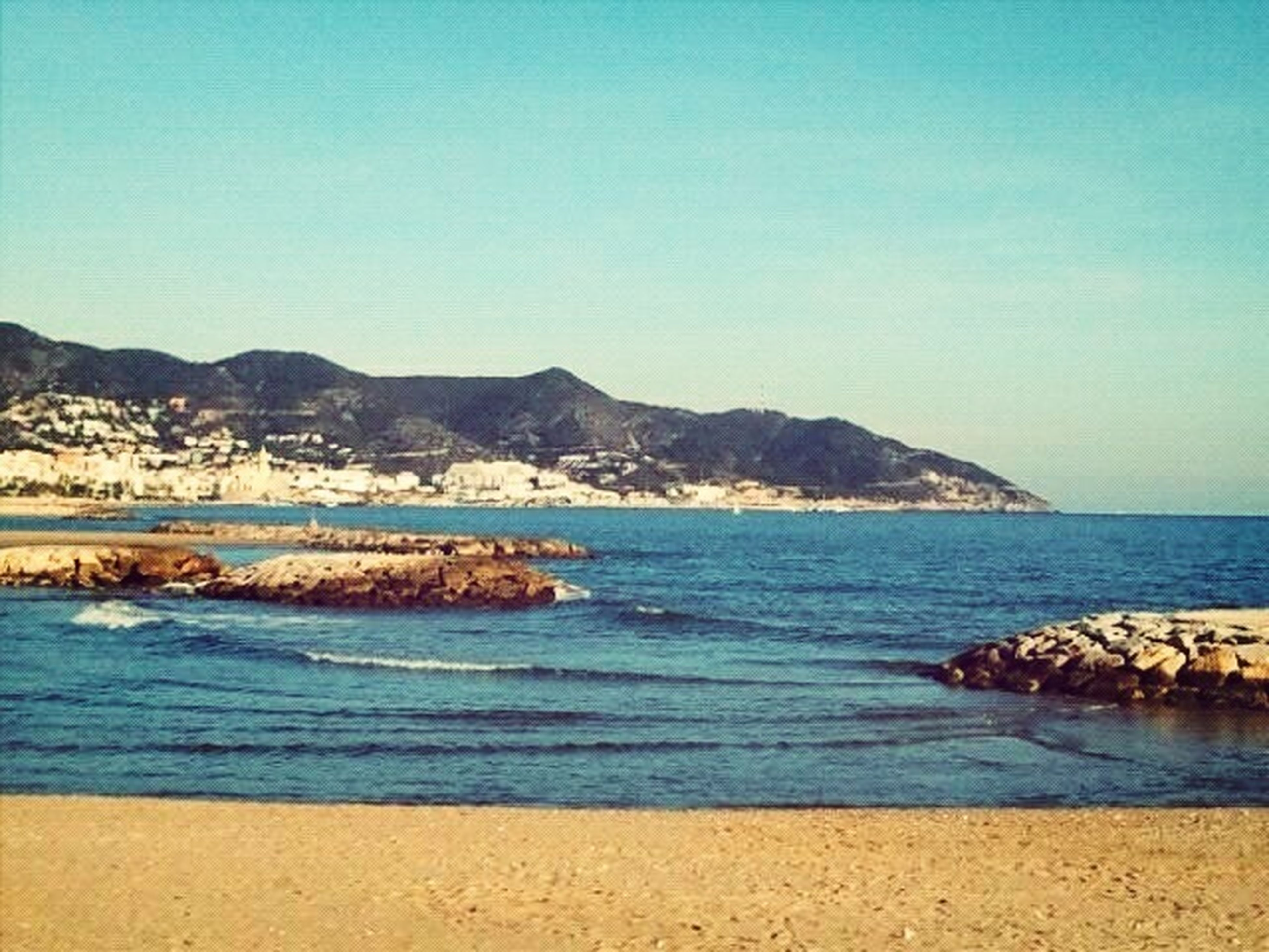 sea, water, clear sky, beach, copy space, blue, scenics, tranquil scene, shore, beauty in nature, tranquility, mountain, sand, coastline, nature, horizon over water, idyllic, wave, outdoors, no people