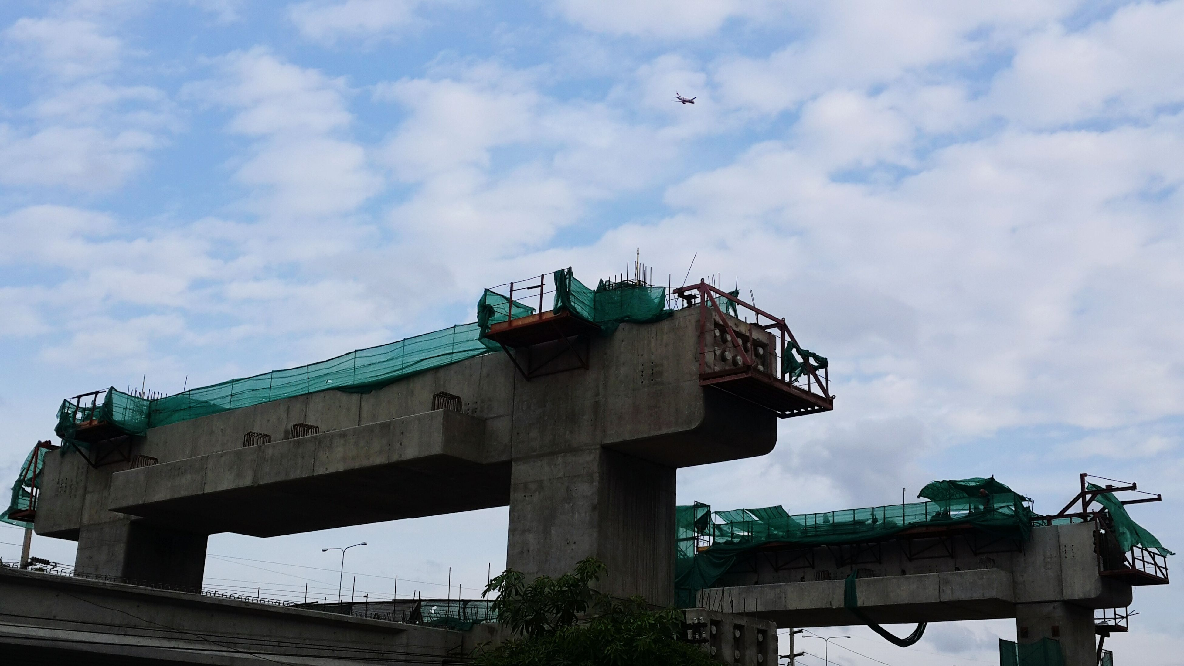 low angle view, sky, built structure, architecture, transportation, bridge - man made structure, cloud - sky, connection, building exterior, cloud, outdoors, day, mode of transport, cloudy, engineering, railing, no people, bird, crane - construction machinery, bridge