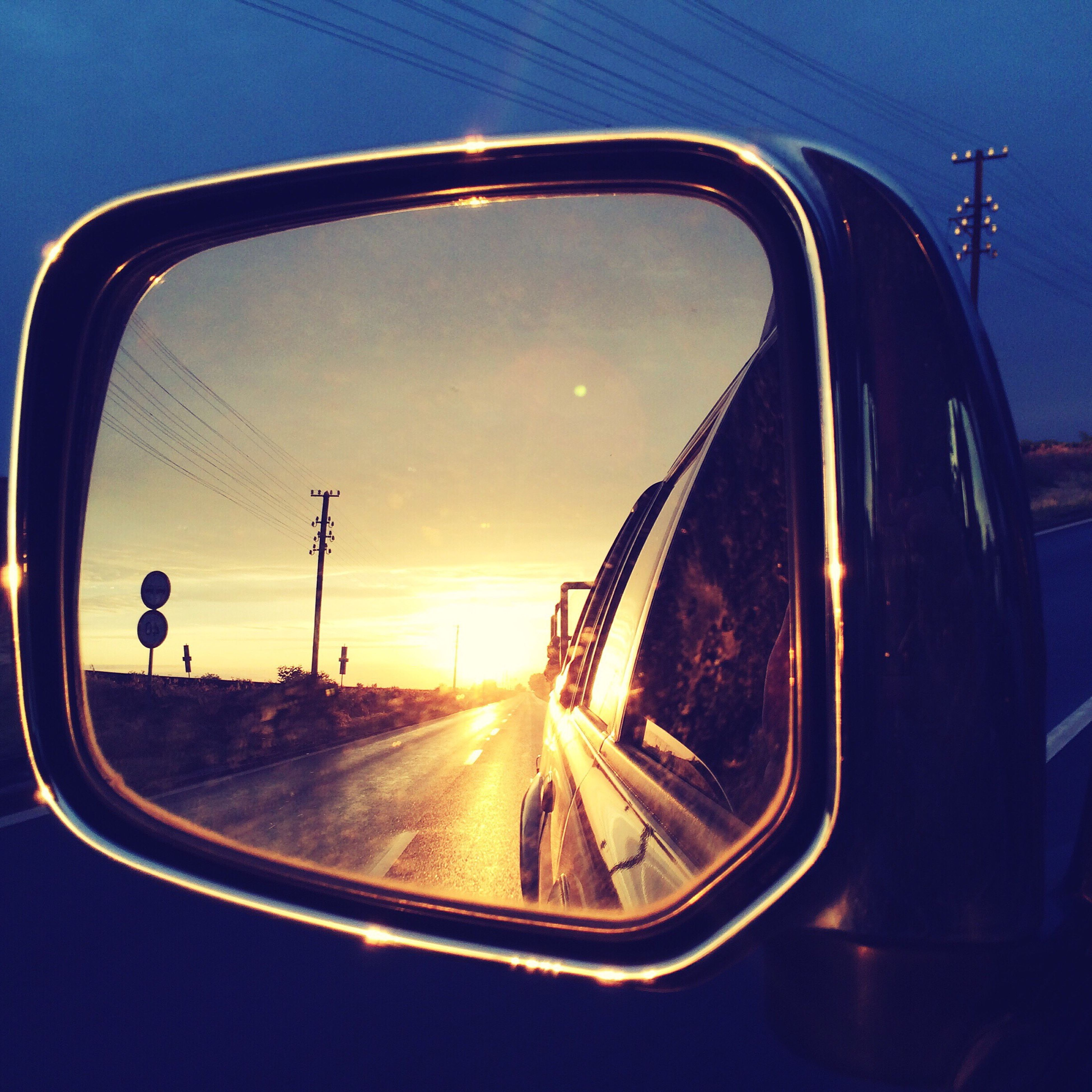 transportation, mode of transport, car, land vehicle, side-view mirror, vehicle interior, sunset, glass - material, transparent, sky, road, reflection, windshield, car interior, travel, sun, on the move, sunlight, part of, window