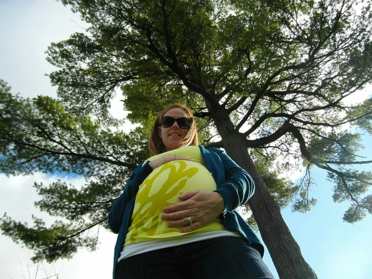 tree, low angle view, sunglasses, looking at camera, one person, standing, three quarter length, casual clothing, day, outdoors, smiling, real people, front view, portrait, leisure activity, sky, happiness, lifestyles, young adult, nature, people