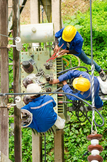 Electrician preparing an oil change a power-transformer Cable Electrician  Engineer Fix  High Power High Voltage High Volts Insulator LINE Maintenance Work Oil Change Procedure Renovate Safety Helmet Transformer Wrench