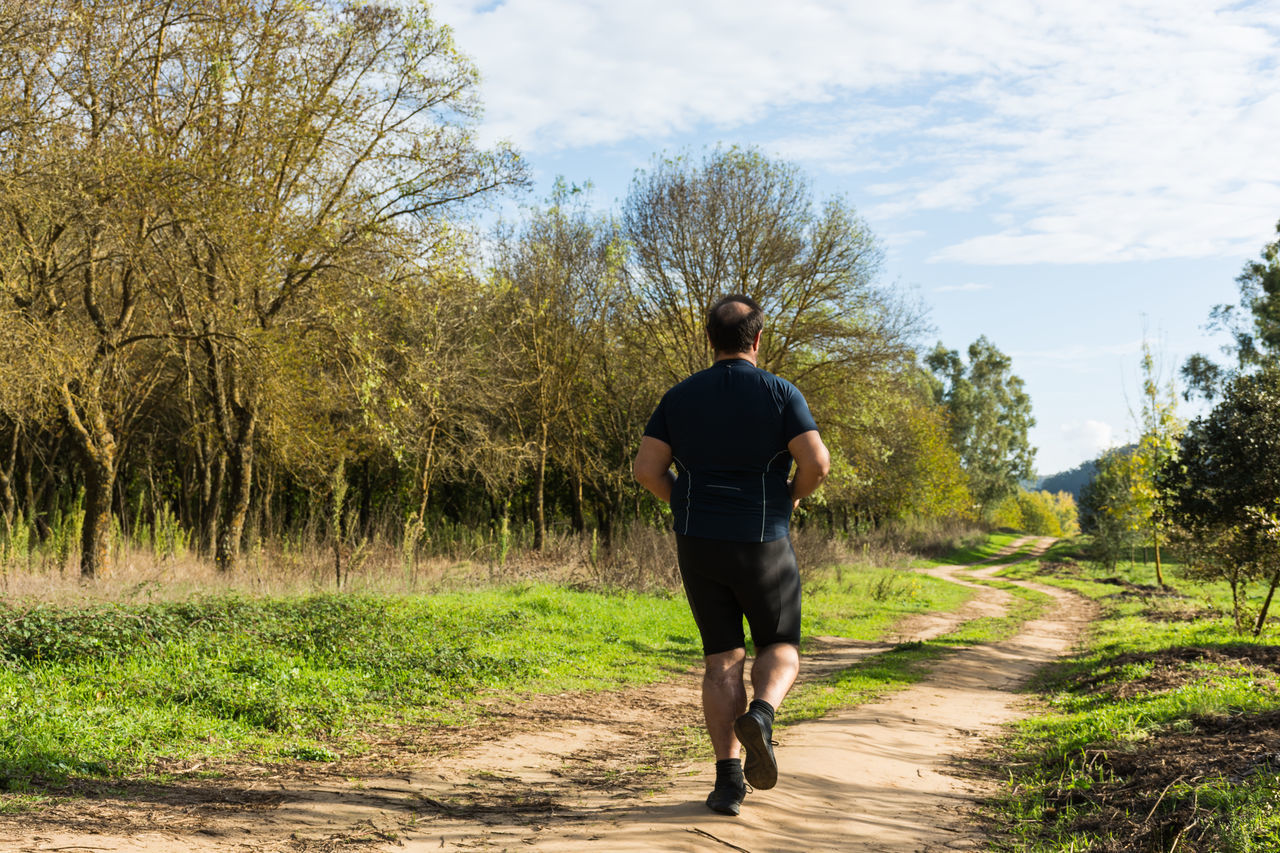 Adult Day Footpath Full Length Grass Lifestyles Men Nature Obese Obese Boy Obese Man Obesity One Man Only One Person Only Men Outdoors Overweight Overweighted Real People Rear View Road Sky The Way Forward Tree Walking