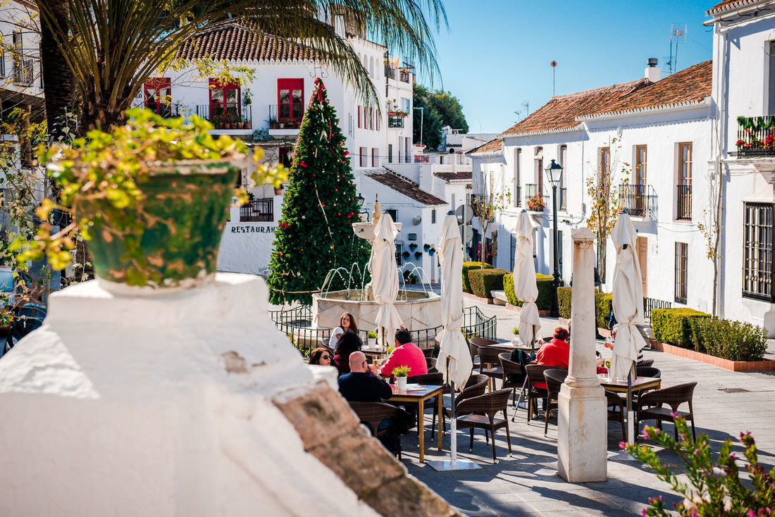Mijas, Spain- January 5, 2014: Tourists sitting in a sidewalk cafe on central street of Mijas. Mijas is a lovely Andalusian white village on the Costa del Sol. Spain Andalucía Mijas Plants SPAIN Siesta Sitting Square Tables And Chairs Building Exterior Built Structure Cafe City Costa Del Sol Editorial  Europe Outdoors Outdoors Cafe People Sidewalk Cafe Street Sunny Day Travel Destinations Village White Village Whitewashed Houses
