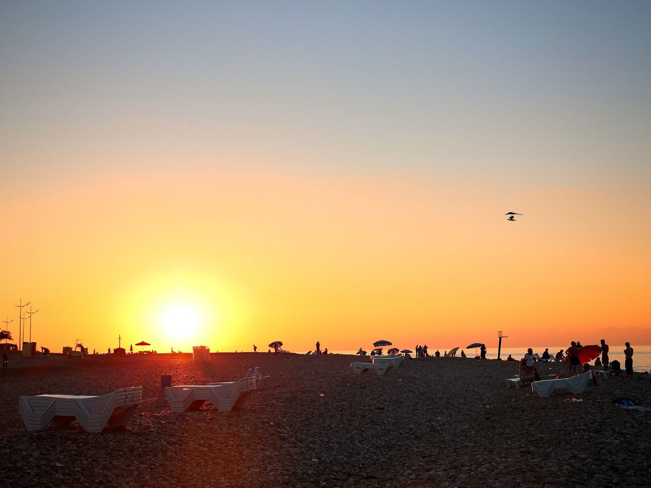 sunset, beach, sand, sky, sea, leisure activity, nature, outdoors, real people, vacations, sun, clear sky, enjoyment, weekend activities, large group of people, flying, silhouette, scenics, sunlight, beach volleyball, beauty in nature, leisure, lifestyles, horizon over water, day, people