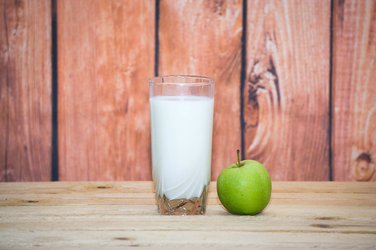 drink, healthy eating, drinking glass, milk, food and drink, wood - material, freshness, fruit, apple - fruit, table, indoors, food, milk bottle, drinking straw, no people, healthy lifestyle, day, smoothie, close-up