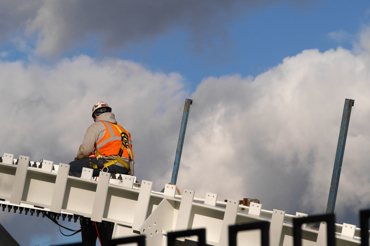Low Angle View Of Worker Sitting At Construction Site Against Sky