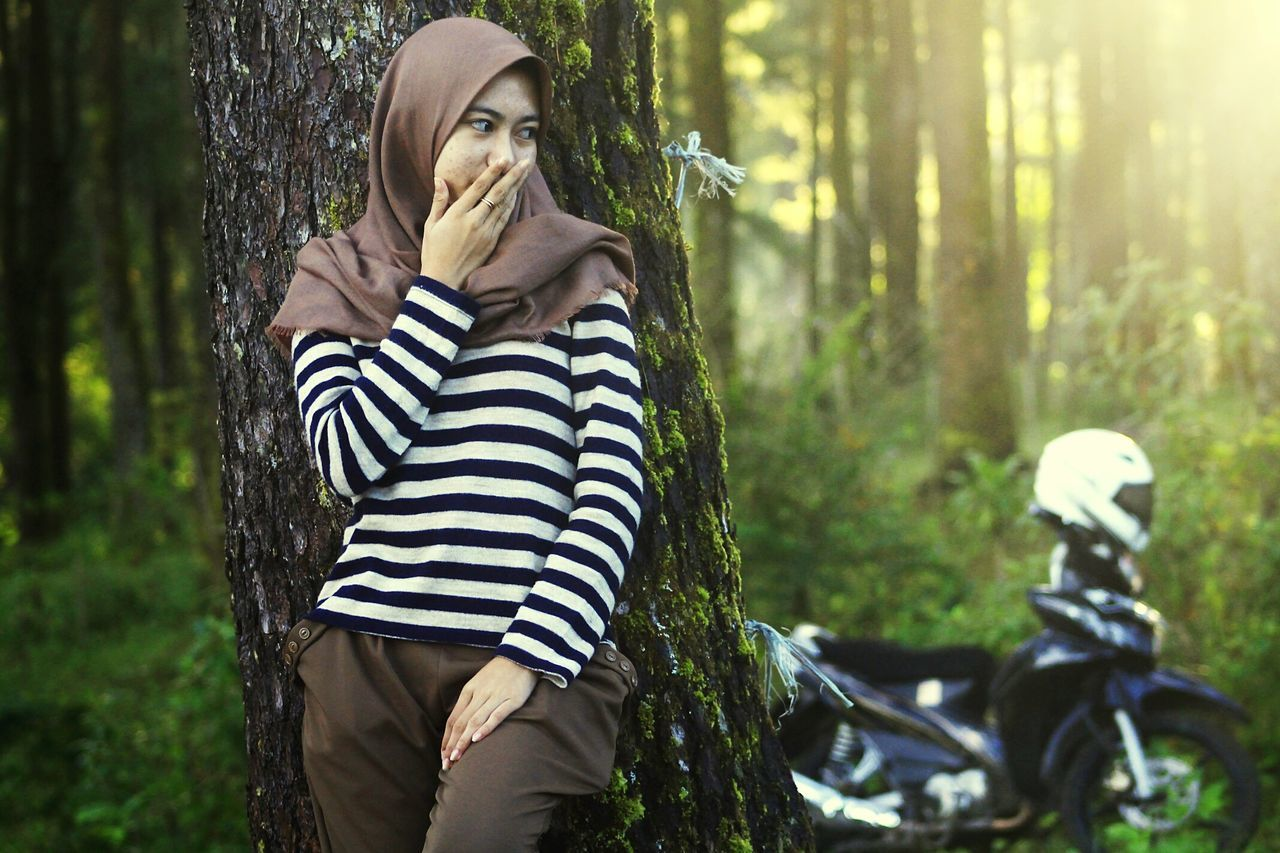 one person, young adult, real people, young women, forest, tree, striped, leisure activity, outdoors, casual clothing, standing, lifestyles, nature, tree trunk, day, focus on foreground, beautiful woman, women, adult, adults only, people