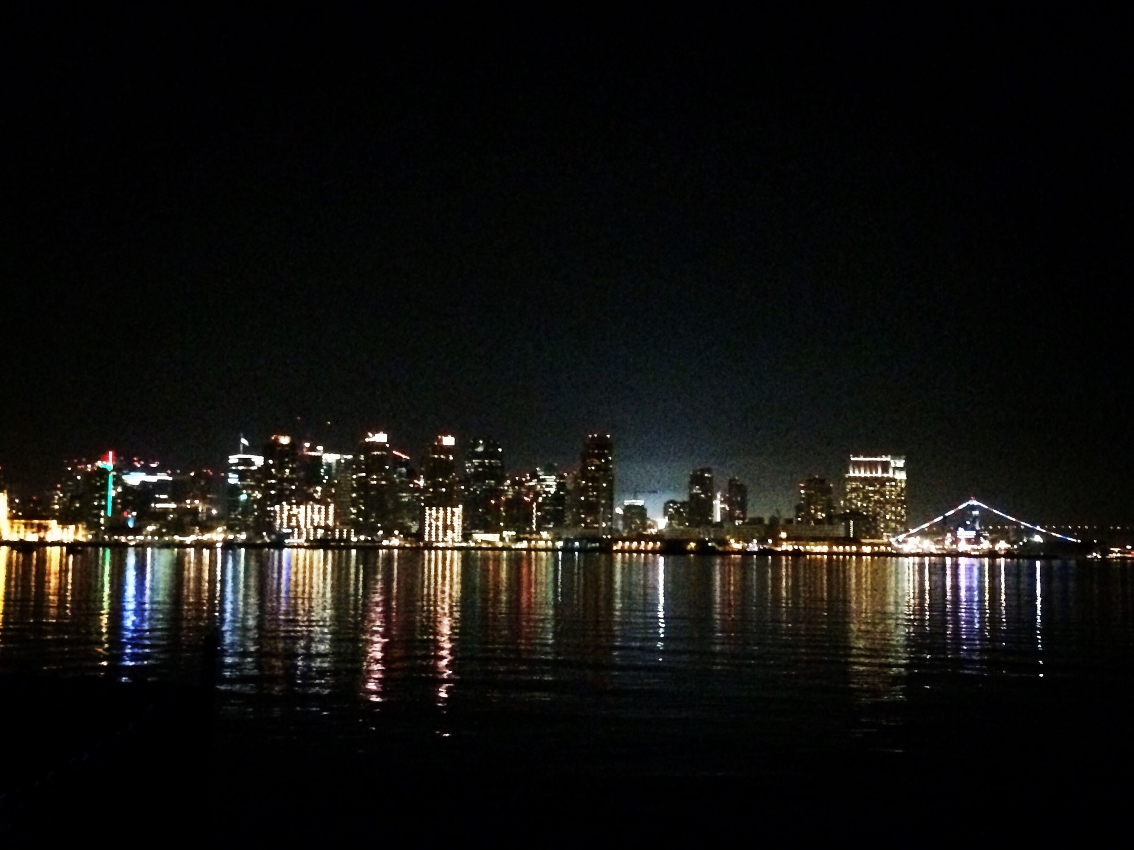 illuminated, night, water, waterfront, city, building exterior, architecture, built structure, reflection, river, cityscape, sea, skyscraper, clear sky, copy space, sky, urban skyline, modern, no people, outdoors