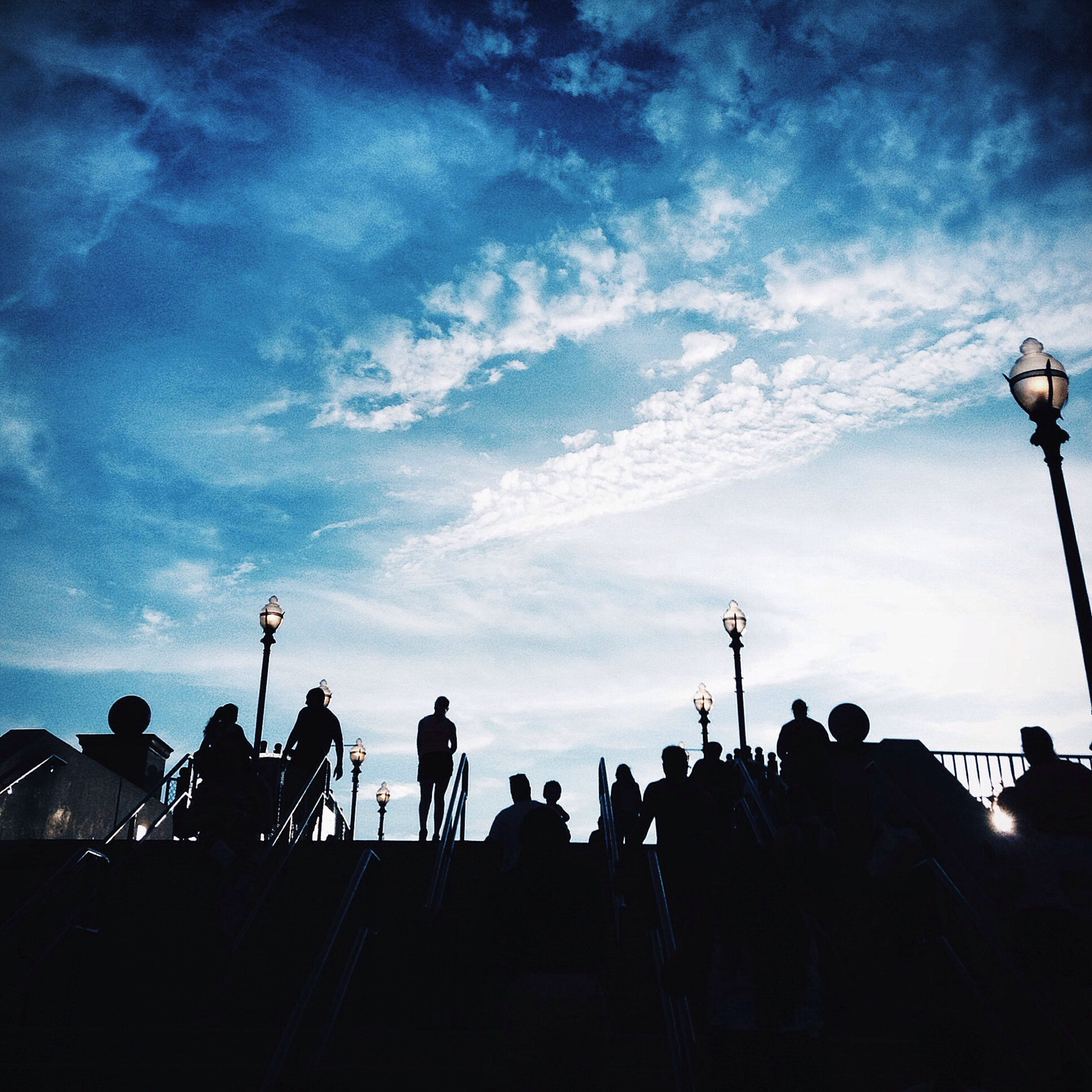 sky, silhouette, low angle view, large group of people, cloud - sky, street light, men, dusk, cloud, blue, person, lifestyles, lighting equipment, leisure activity, outdoors, cloudy, nature, mixed age range, built structure