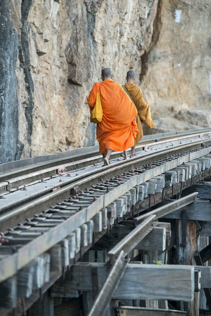 Rear View Of Monks Walking On Railway Bridge By Rocky Mountains
