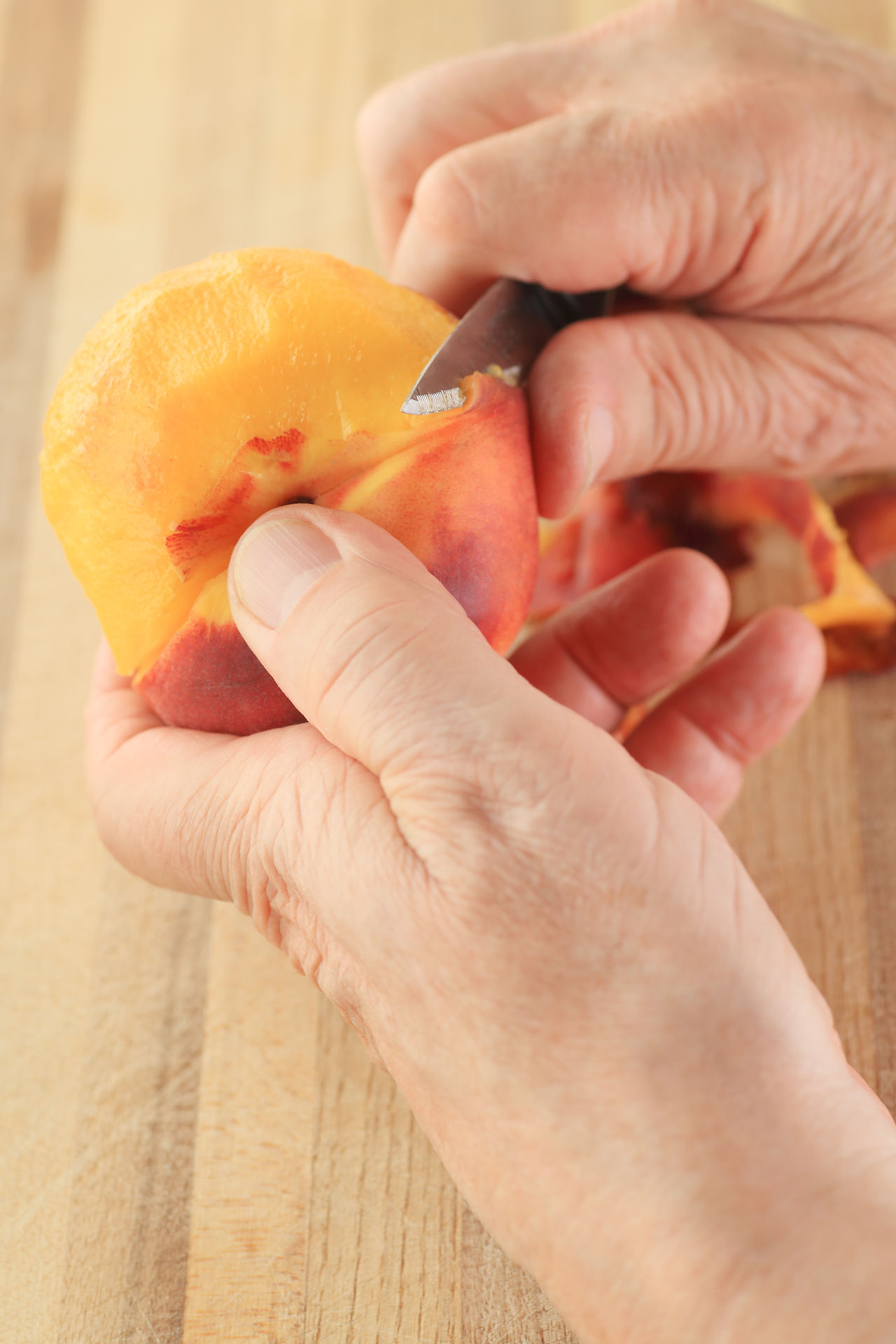 Senior removes peel from peach Close-up Cutting Board Fingers Food Food Preparation Fresh Fruit Hands Healthy Eating Holding Juicy Man Natural Light One Person Orange Color Overhead Peach POV Snack Sweet Textures Using Knife Vertical Wood Surface