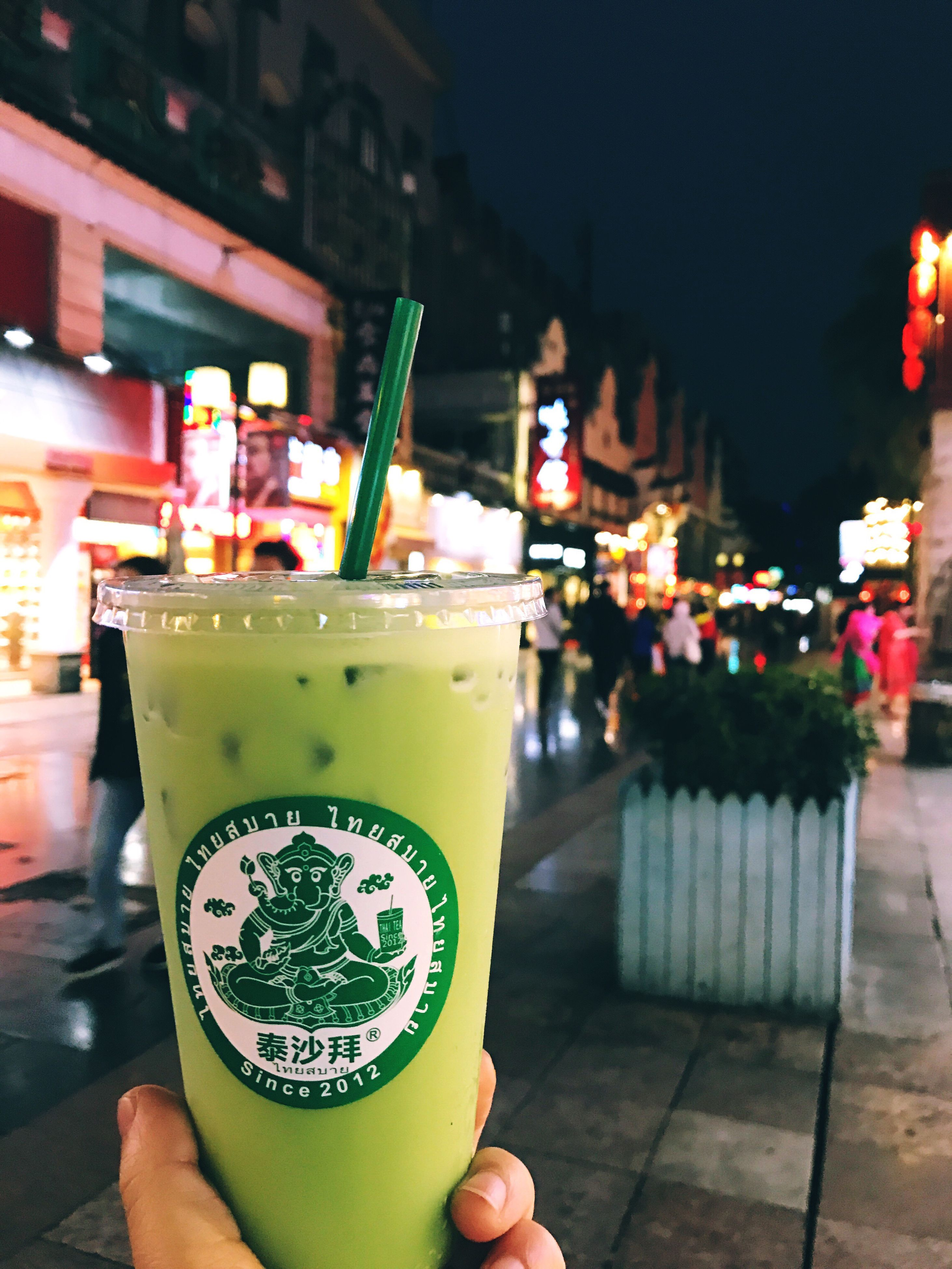 night, refreshment, illuminated, freshness, food and drink, drink, green color, real people, drinking straw, human body part, drinking glass, human hand, close-up, outdoors, people