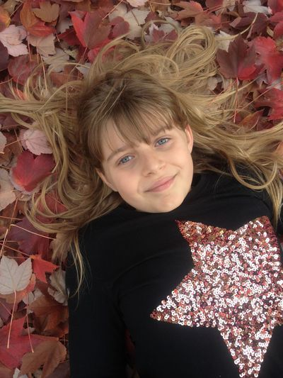 Young girl laying in colorful Fall leaves Blond Hair Child Colorful Leaves In Autumn Fall Beauty Fall Leaves Leaves Looking At Camera One Girl Only One Person Portrait