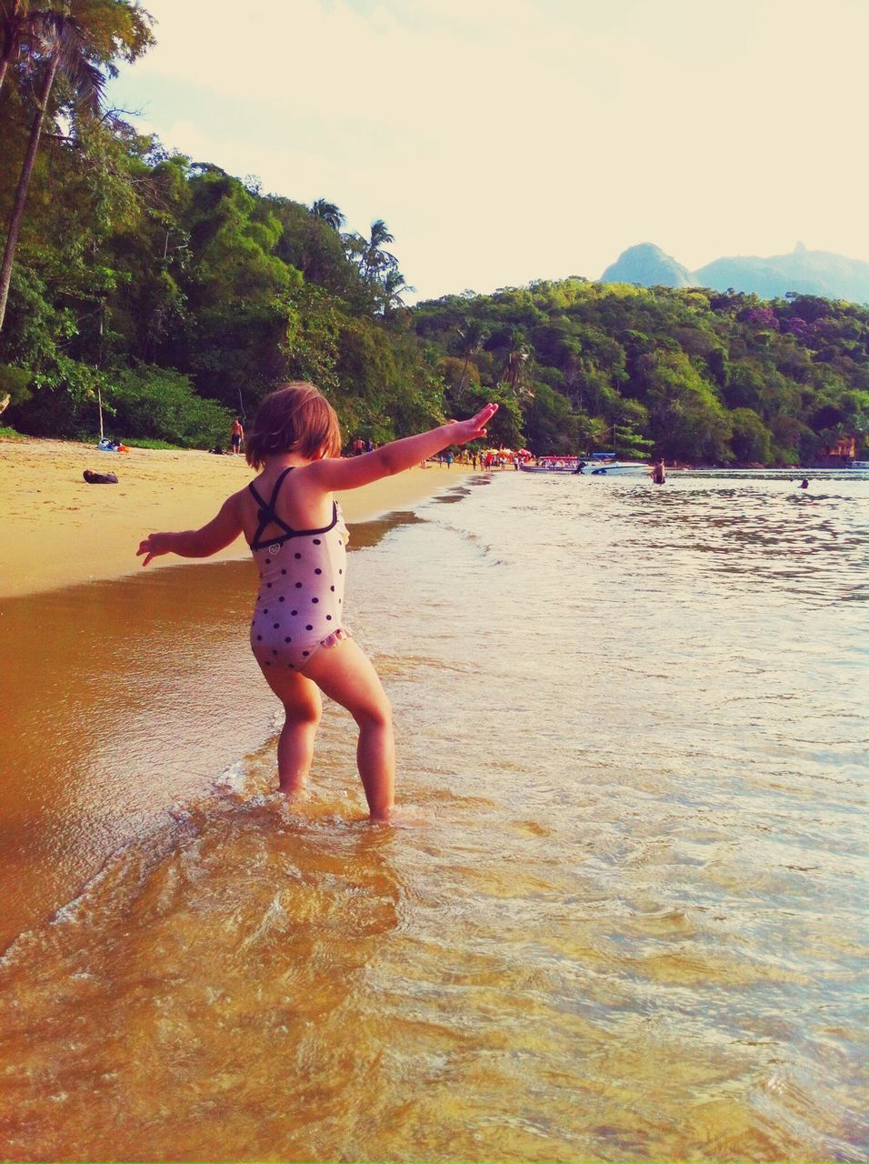 Rear View Of Girl With Arms Outstretched At Shore