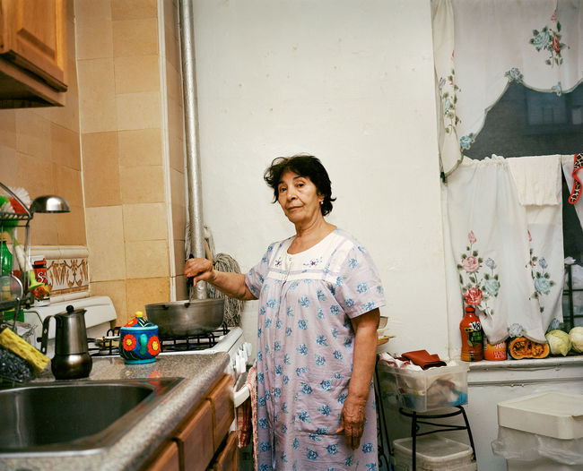 """Mi madre (My Mother) was the first of her eight siblings to come to Nueva York (New York). In 1979, she embarked on her first viaje (trip) with Tia Glady and Abuela Toña while her seven brothers and sisters momentarily stood behind. Their first destination was a neighborhood in the northern portion of New York City borough of Manhattan, Washington Heights where they shared an apartment with her aunt, uncle, and two cousins. I asked Mami why she left the Dominican Republic. """"For a better life, Adeline. Nosotros no teniamos nada en la Republica Domincana. Venir aquí era como un sueño (We didn't have anything in the Dominican Republic. To come here was like a dream). She continued in English with an accent, """"I wanted to come and work here and become somebody in life."""" When Mami left the Dominican Republic she was a 17-year-old high school student entering the 11th grade. When she came to Nueva York she could not continue her education immediately. She said to me in Spanish: """"I had to work and help mama so that we could ask for my brothers and sisters to come. There were a lot of us so I had to work to help bring them here."""" Dominican Dominican Republic Film Photography Filmcamera Filmisnotdead Haitian Mamiya7 Mamiya7ii Mediumformat Portraits Still Life The Photojournalist - 20I6 EyeEm Awards Washington Heights"""