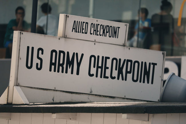 Checkpoint Charlie Berlin Berliner Ansichten Canonphotography Checkpoint Checkpoint Charlie  Checkpointcharlie Close-up Eye4photograghy Focus On Foreground Germany Information Information Sign Kalter Krieg Kreuzberg No People Text Us Army Vintage