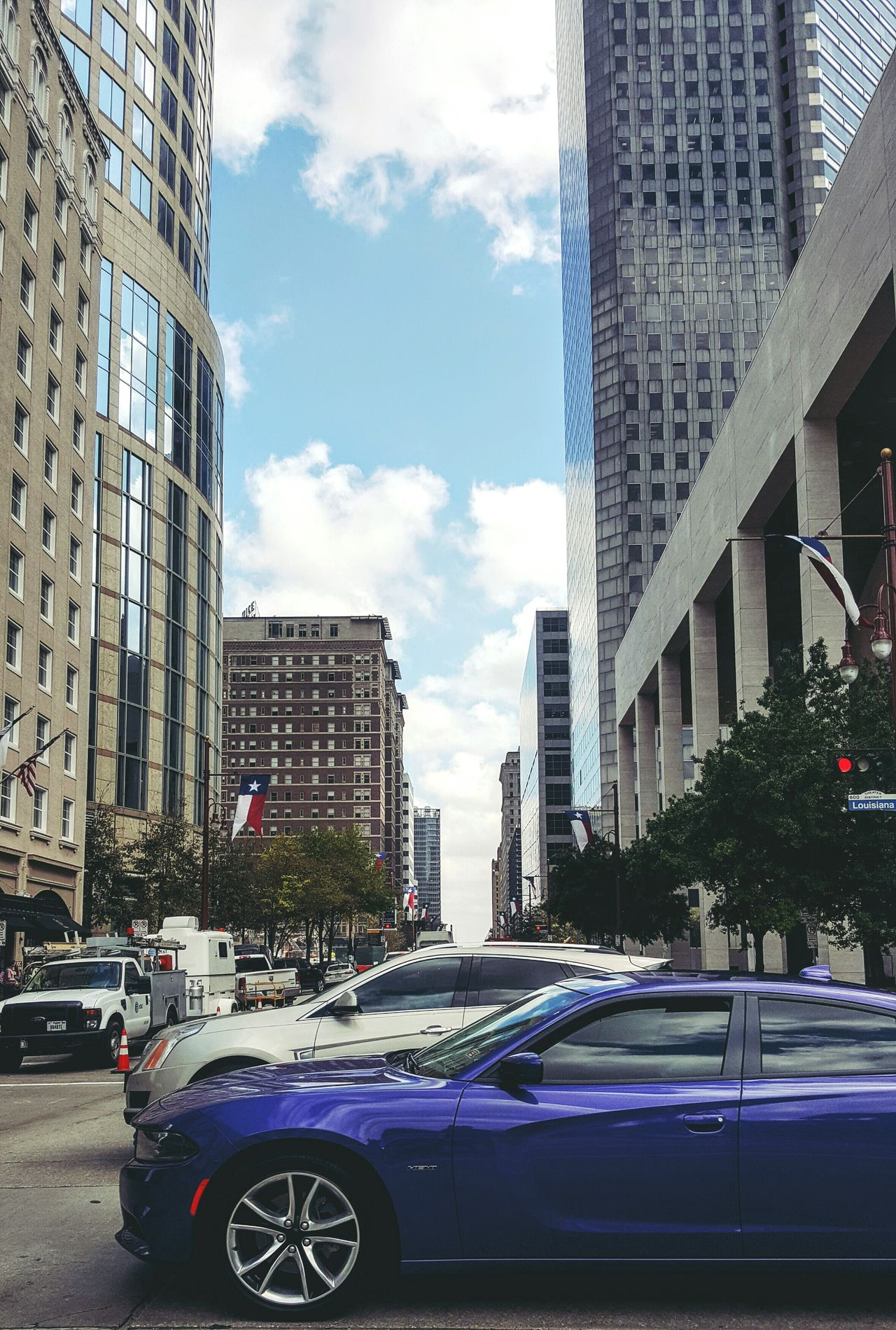 Downtown Houston and a smartphone EyeEmNewHere City Car City Street Architecture Building Exterior Skyscraper Transportation City Life No People Street Day Outdoors Sky Houston Texas Downtown Houston Travel Destinations First Eyeem Photo