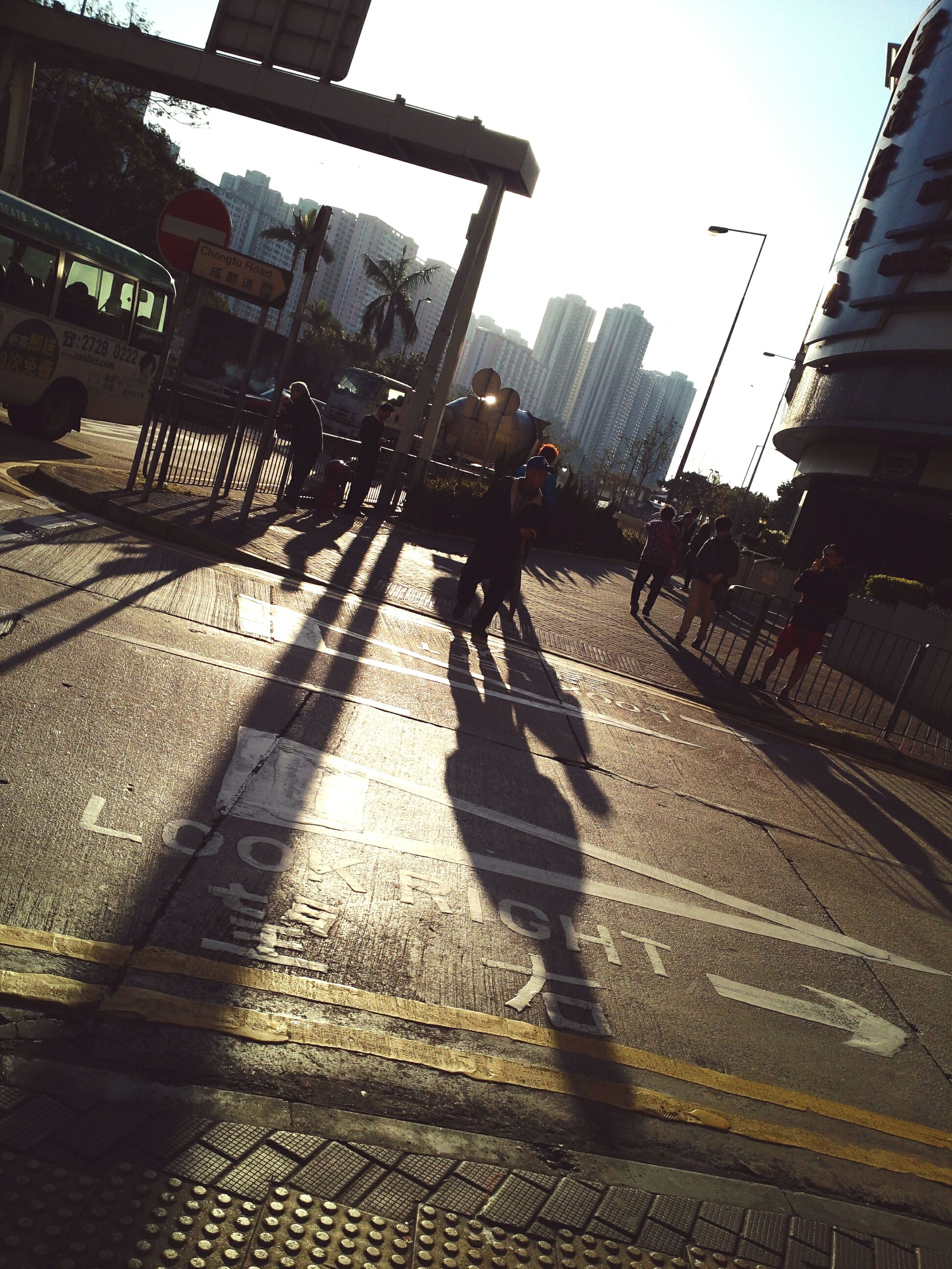 shadow, built structure, architecture, building exterior, sunlight, silhouette, city, lifestyles, men, walking, street, low angle view, leisure activity, city life, sky, unrecognizable person, sunny, person